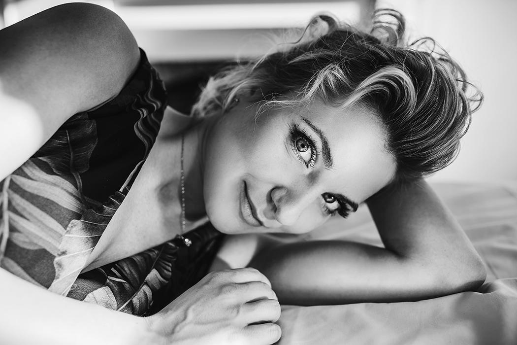 Une femme sur le lit se penche sur l'objectif de la caméra
