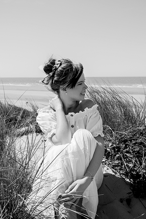 Une femme en robe blanche est assise sur la plage et regarde la mer