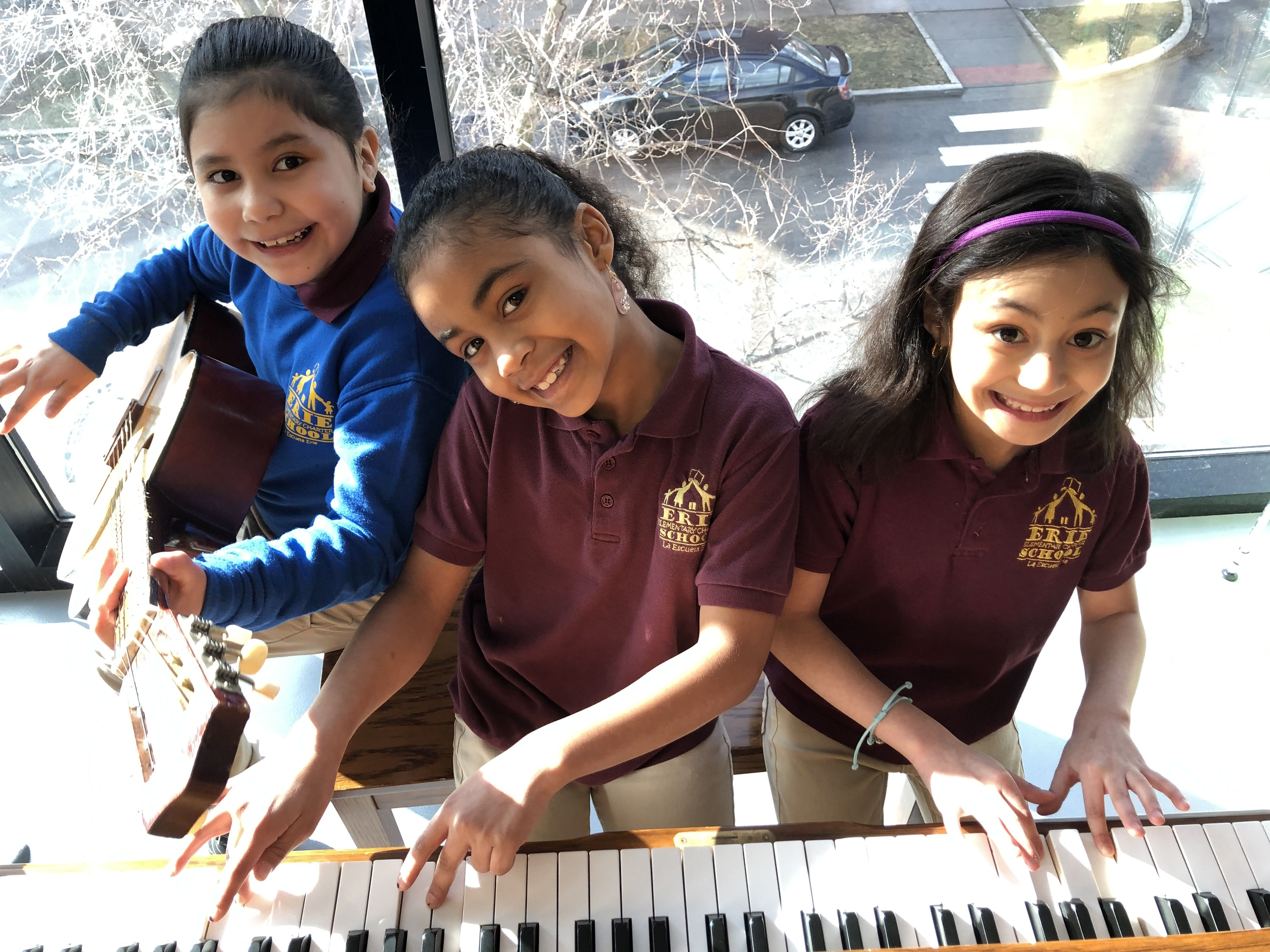 Students learning piano and guitar in music class.