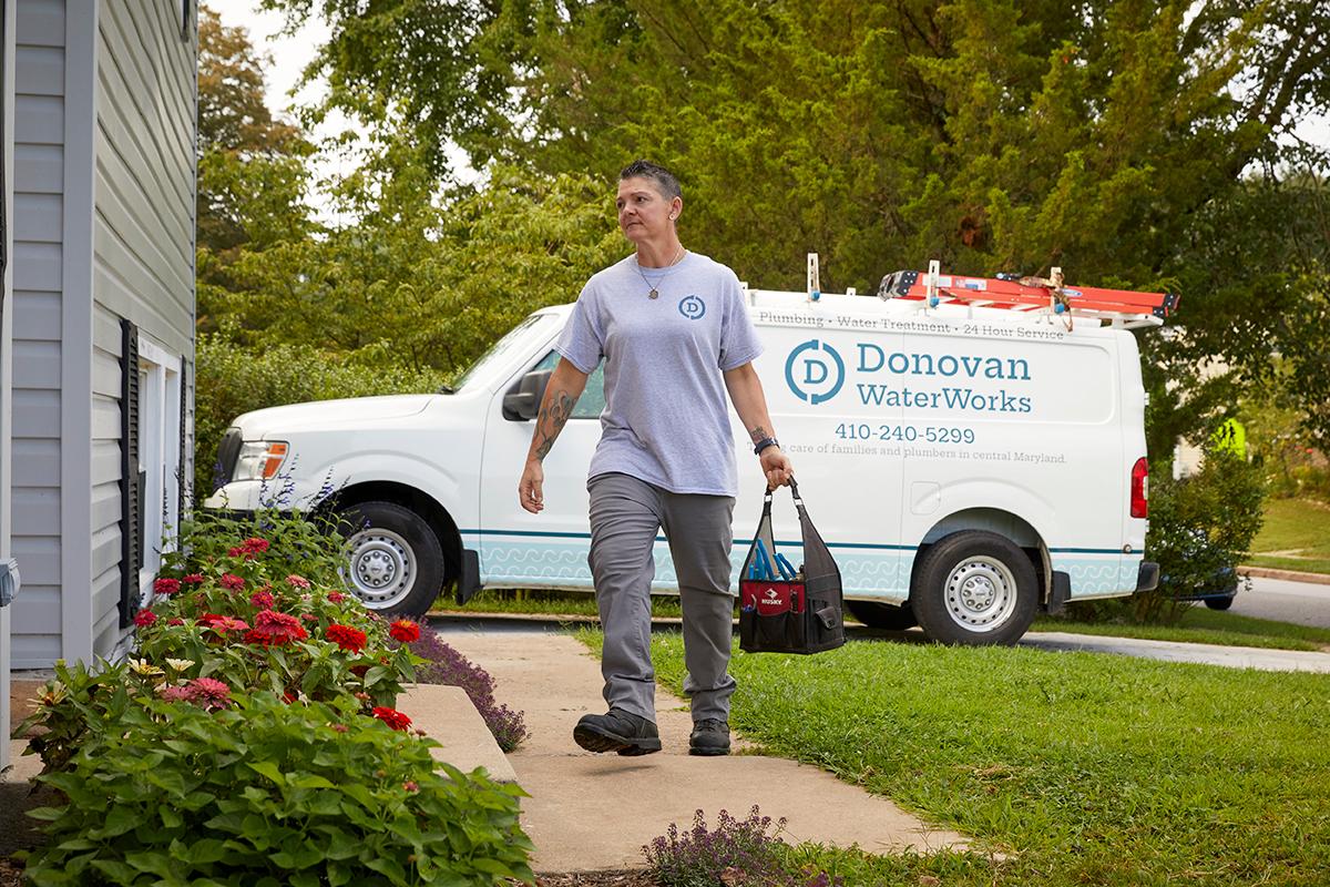 Professional plumber walking to home
