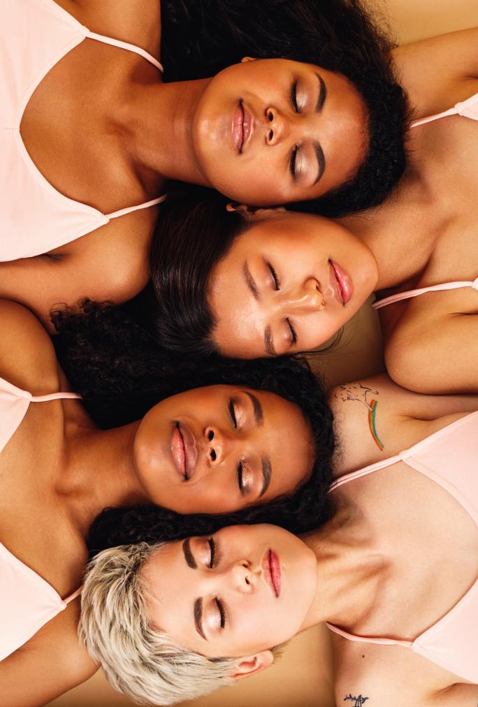 4 women laying down eyes closed
