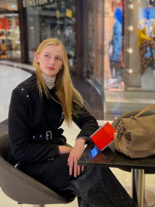 woman seating at a shopping mall holding a neocube breathing clean air