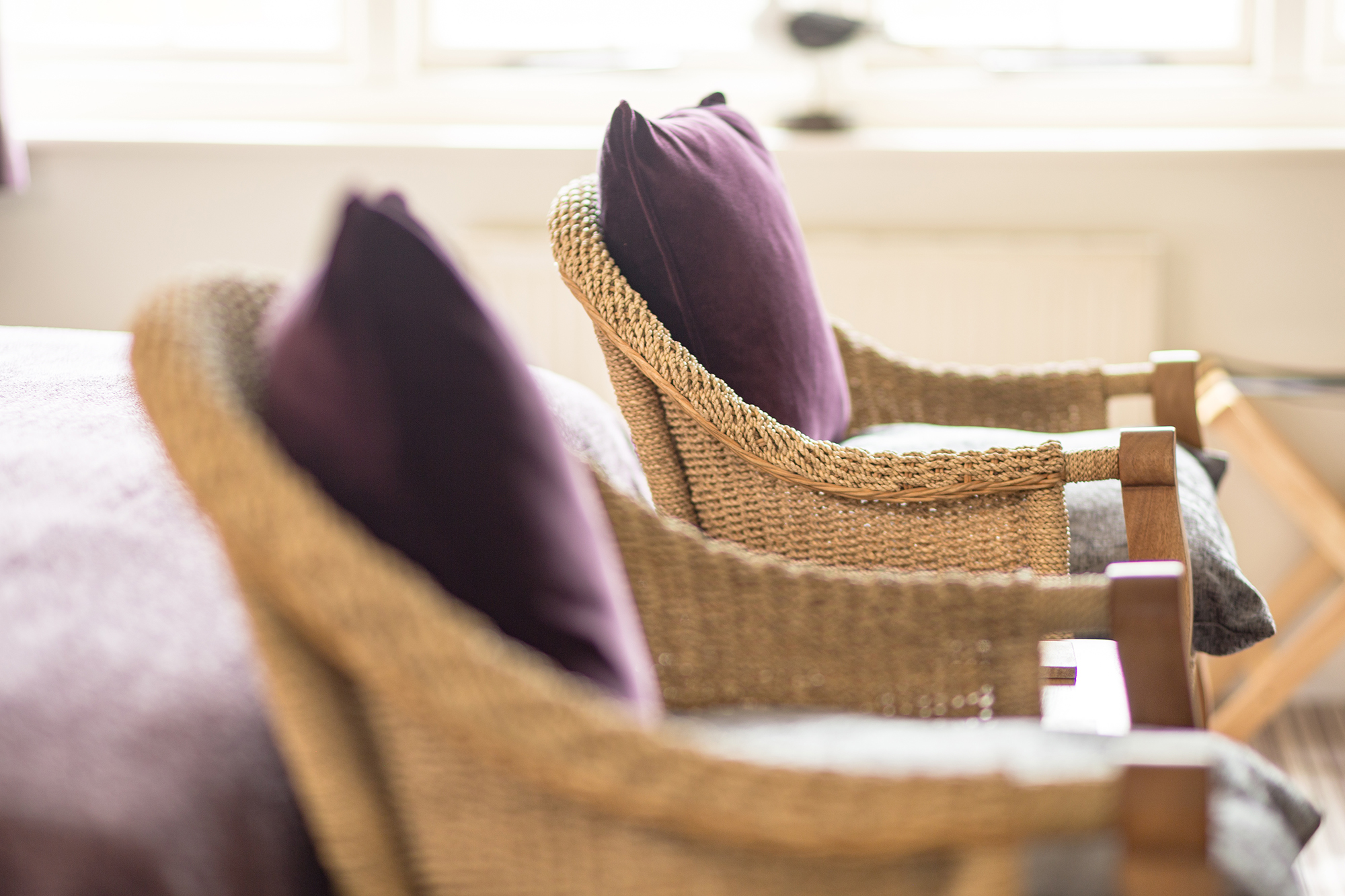 Wicker chairs in front of bed