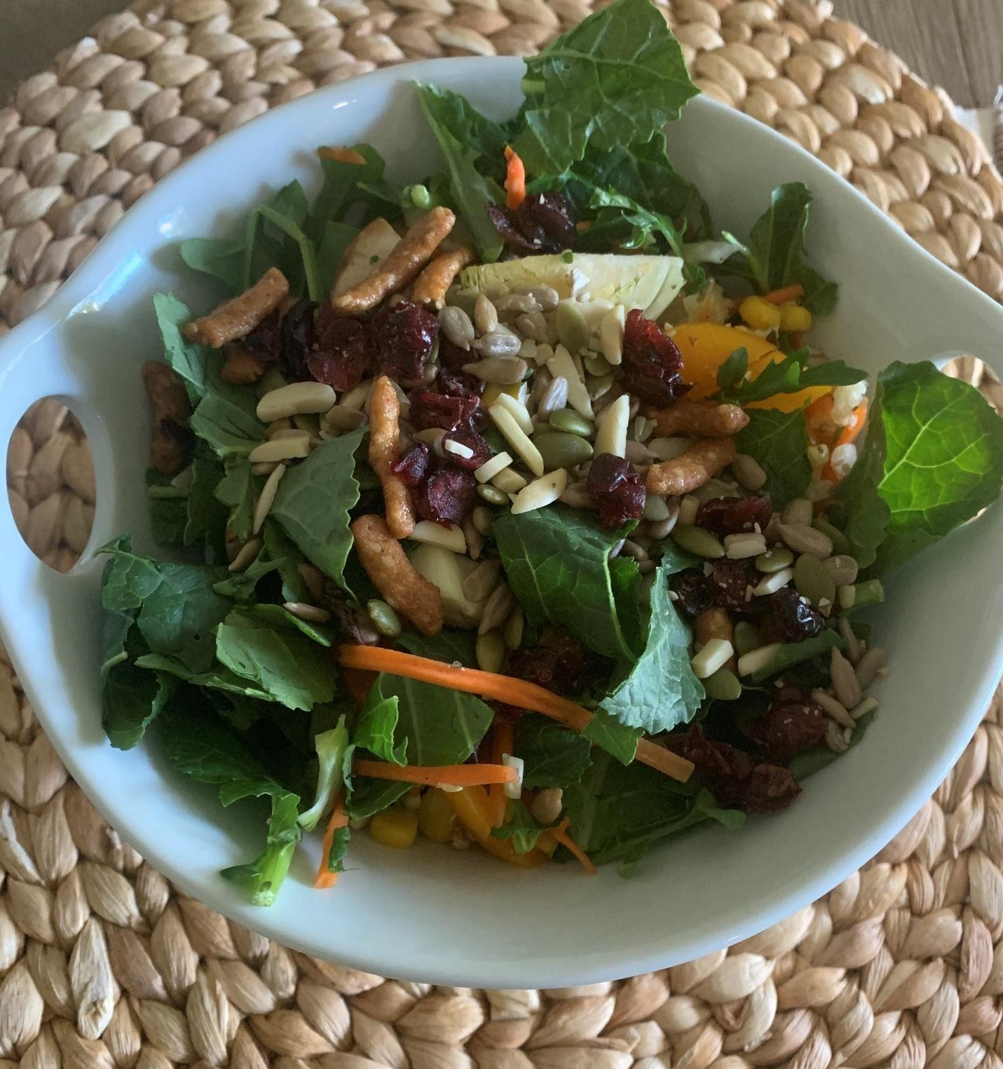 A bowl of salad on a plateDescription automatically generated