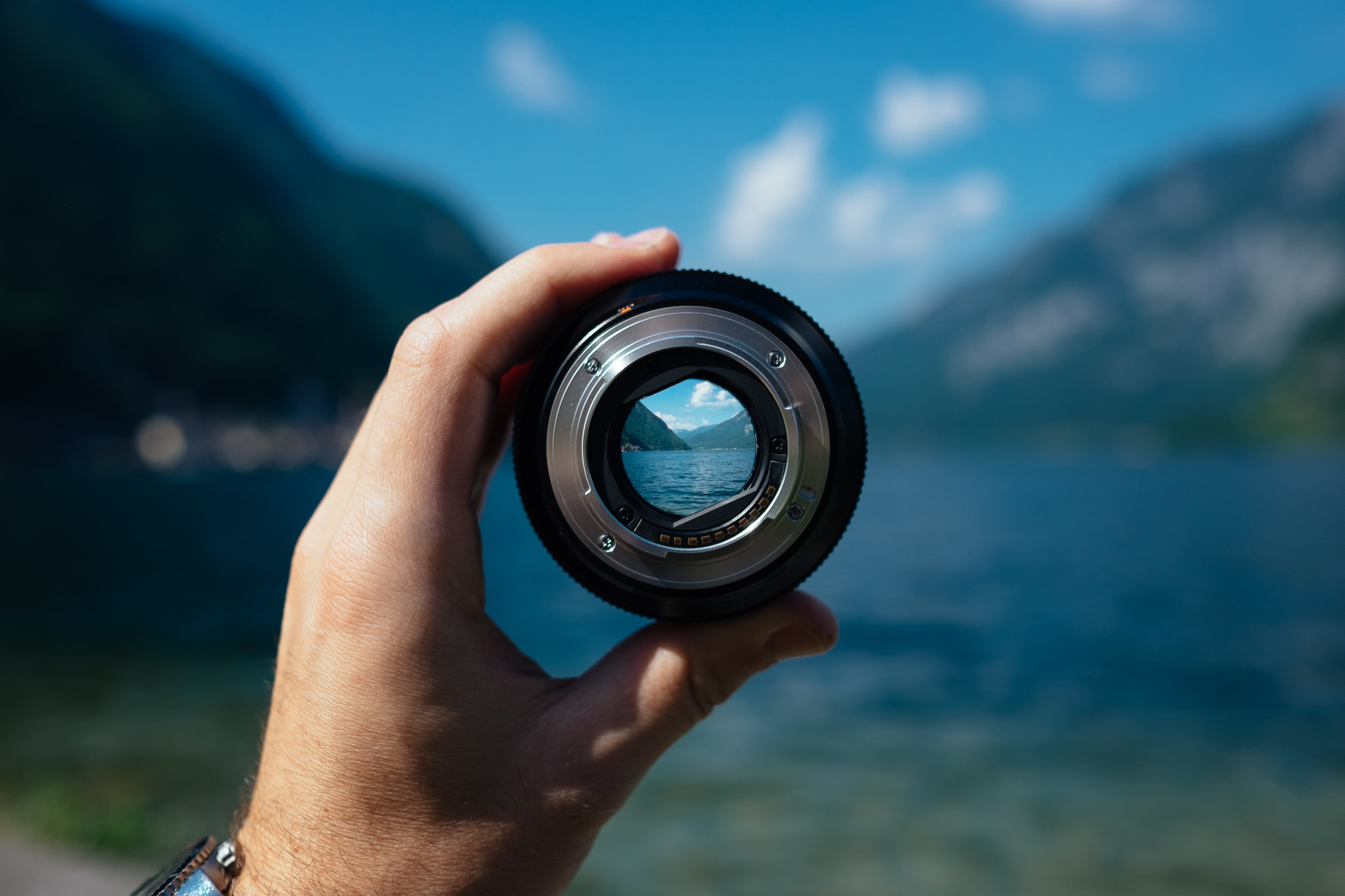 person holding up a lens to make the view in focus