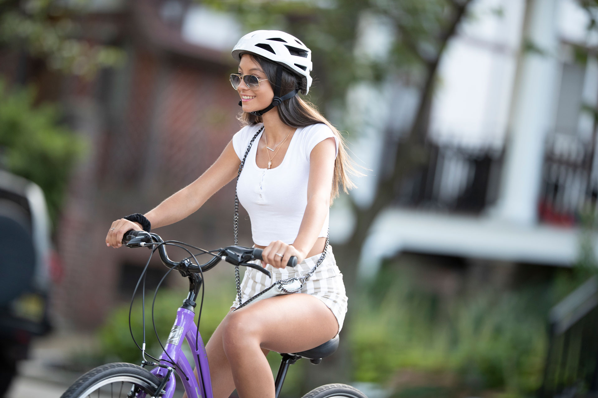 Woman riding bike with helmet on