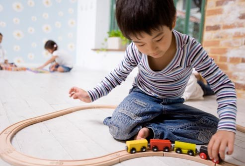 young boy playing with train