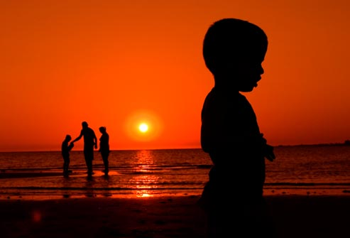 silhouette of family on beach