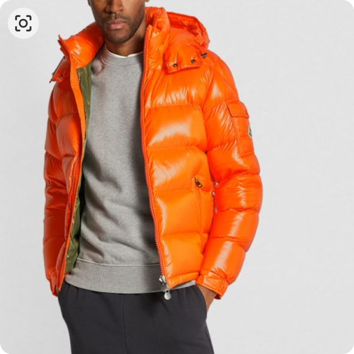 A picture of a man wearing an orange puffer jacket from Moncler, a light grey sweater from Zegna and a pair of black sweatpants from zegna.