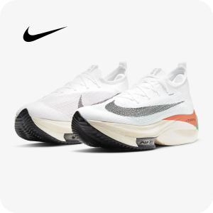 A pair of Nike running shoes in white with grey and orange accents and a black sole.