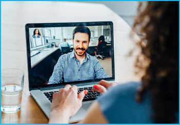 Woman having a virtual meeting on a laptop with a man