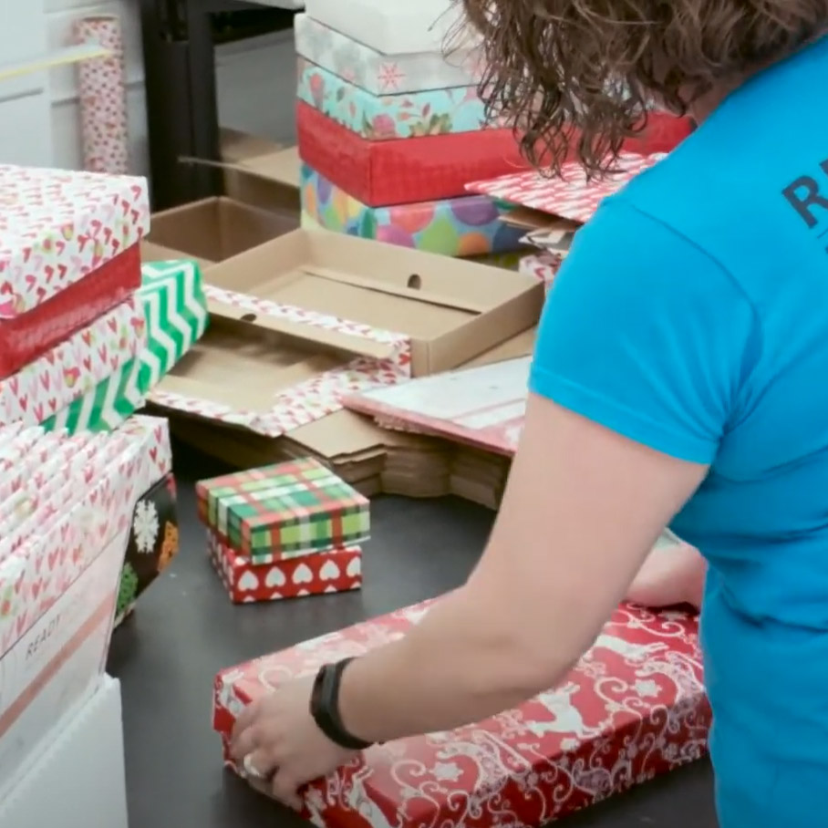 Employee folding and packaging giftboxes.