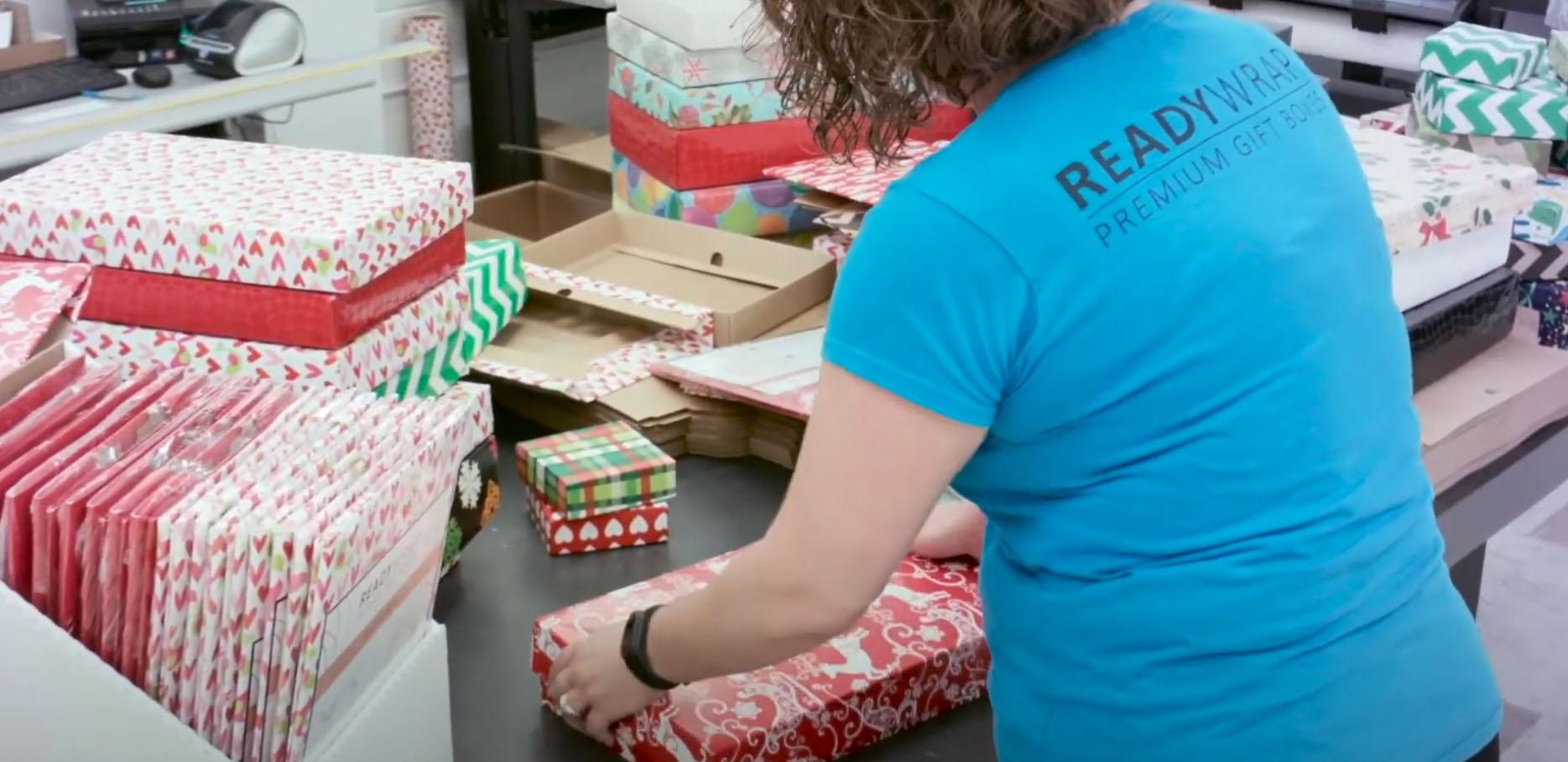 A ReadyWrap employee assembling a chrimstas gift box
