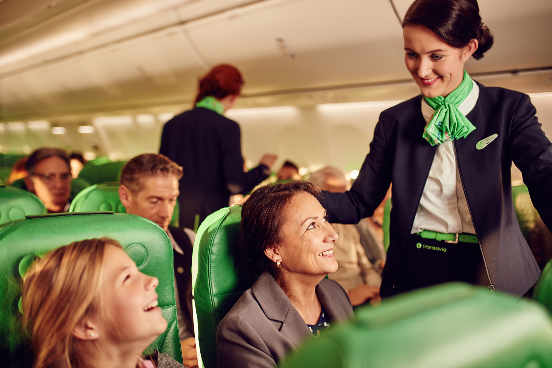 Cabin crew member talking to smiling passengers on a Trasavia filght