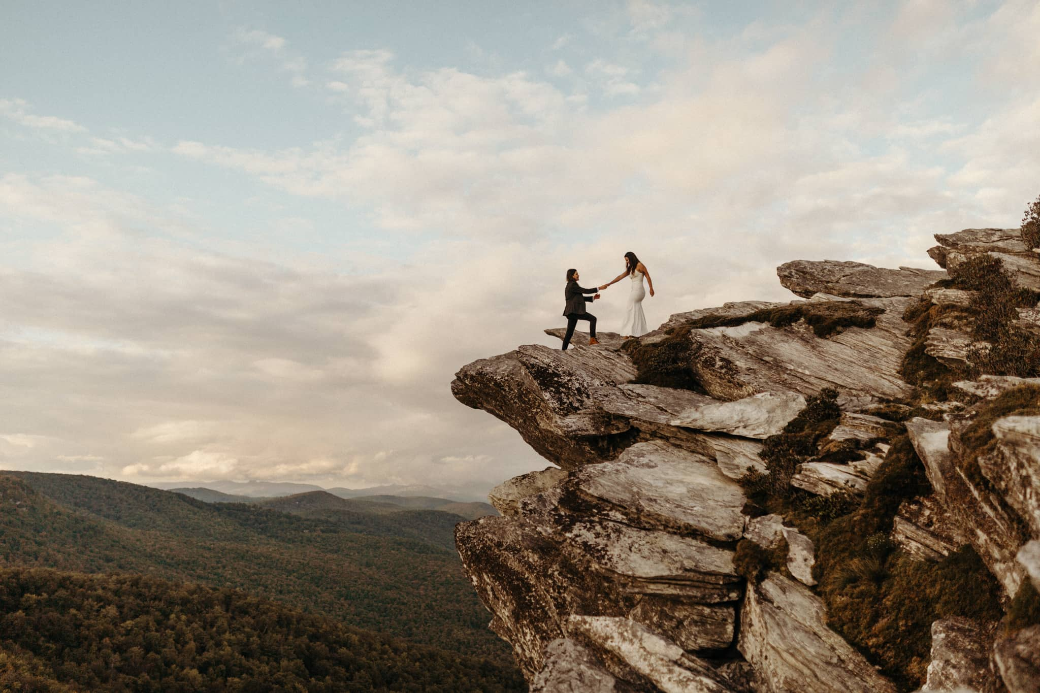 just married couple standing on majestic cliff. photo by Victoria Selman