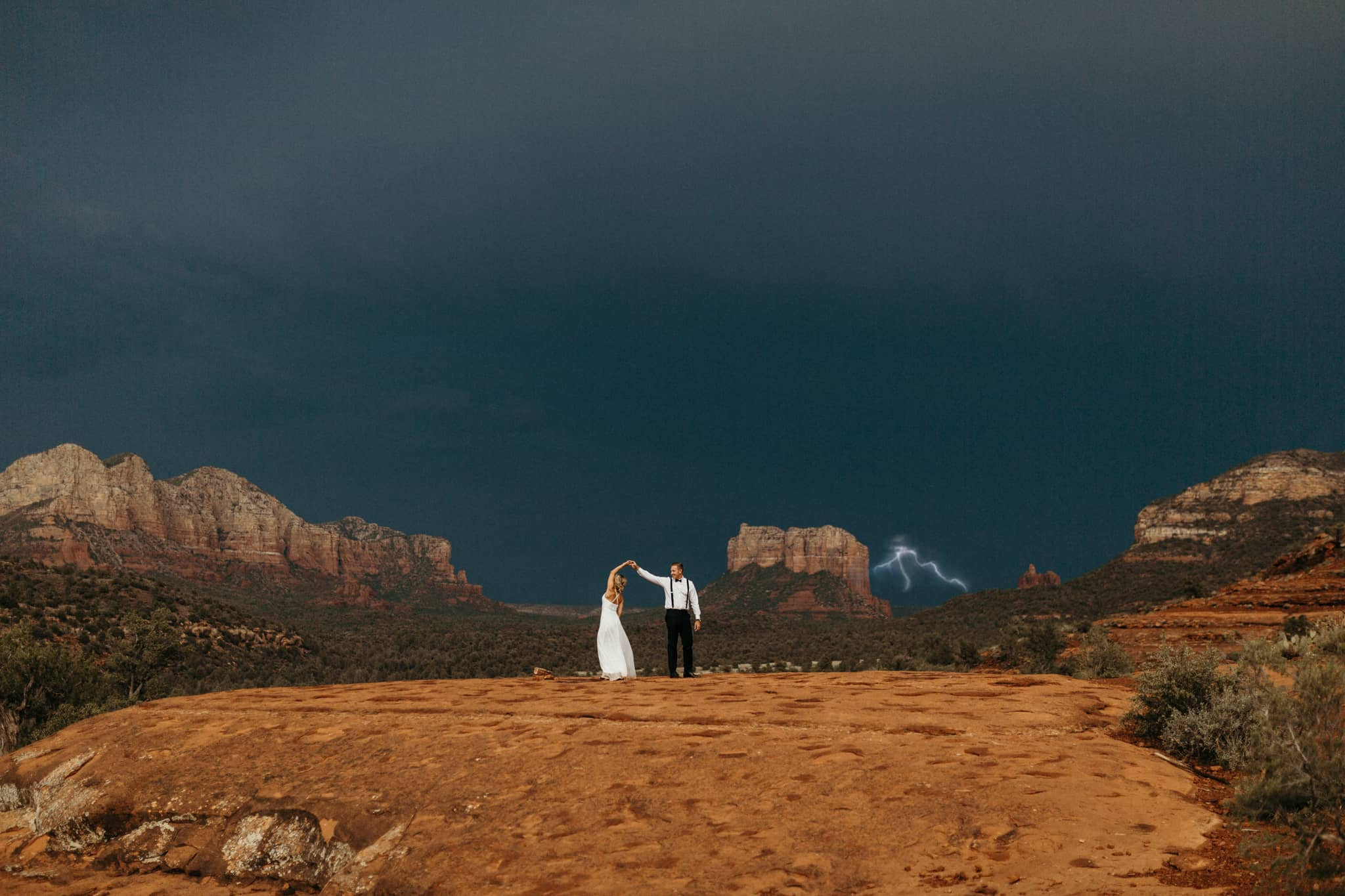 couple dances in the desert while lightning strikes in the background. Photo by Victoria Selman