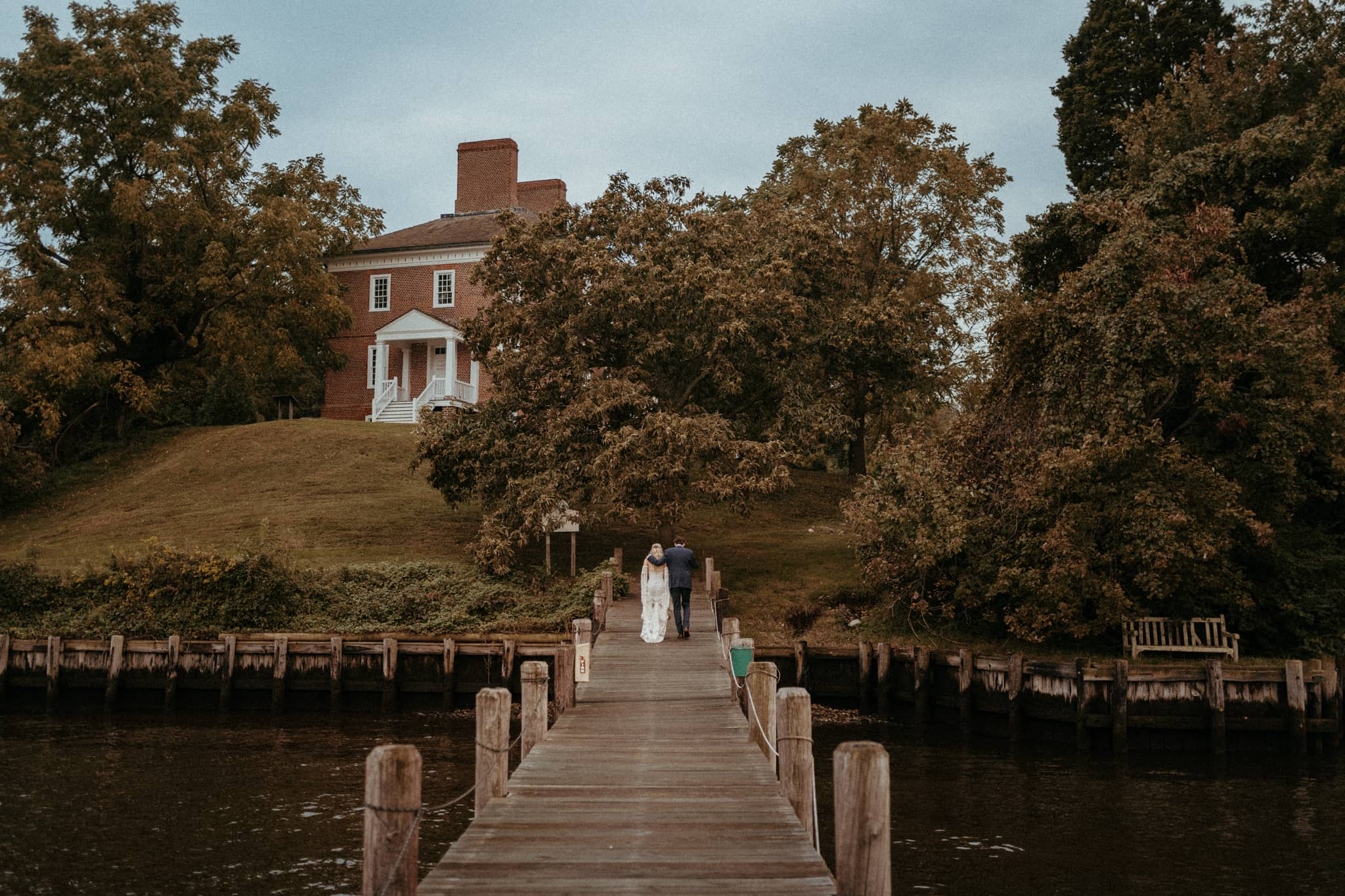 just married couple walks off dock at Historic Londontown. Photo by Victoria Selman.
