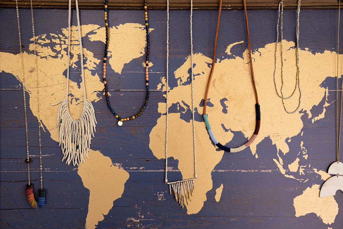 necklaces draped over a map in mango + main