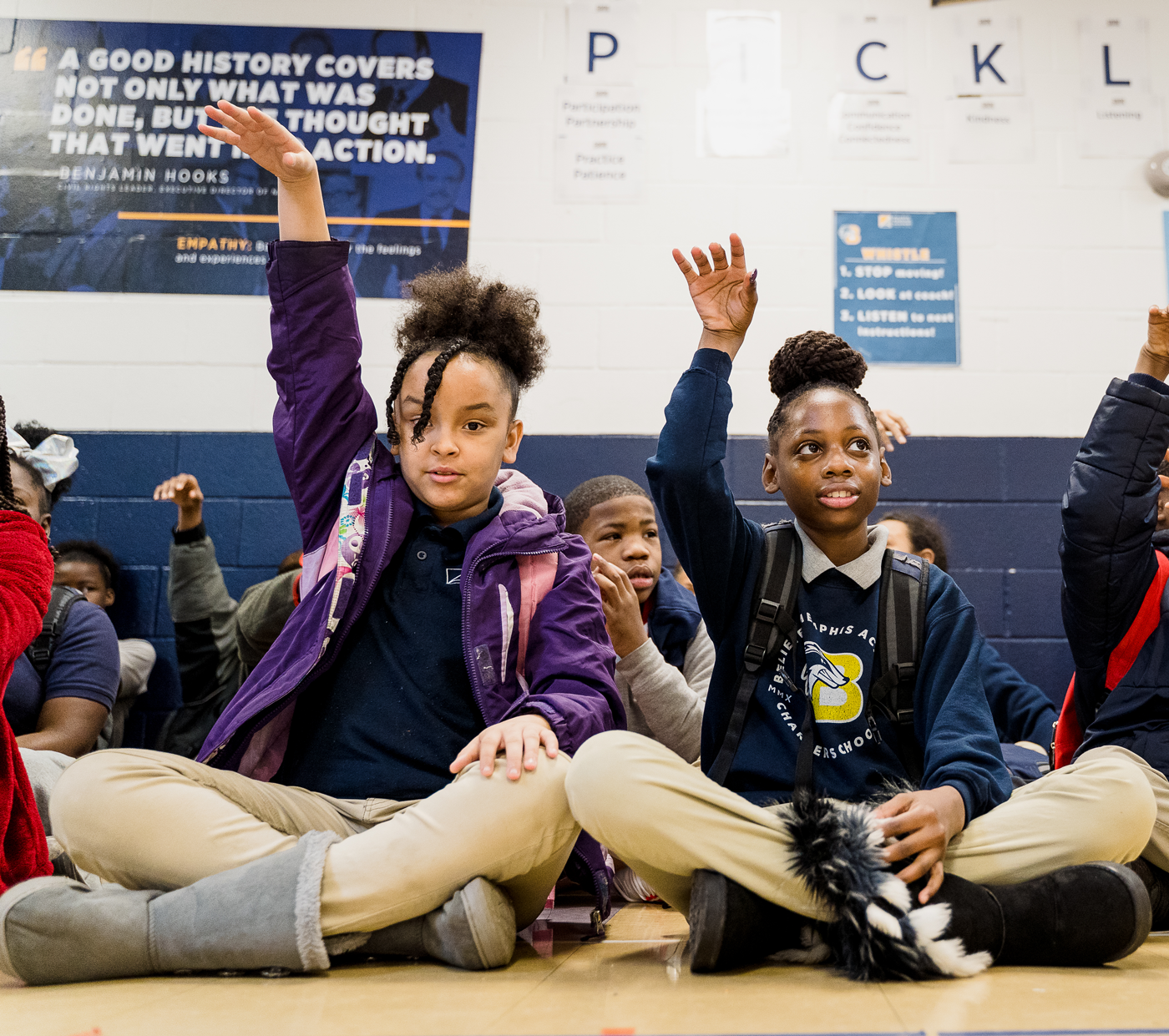 Students raising hands during school wide event.