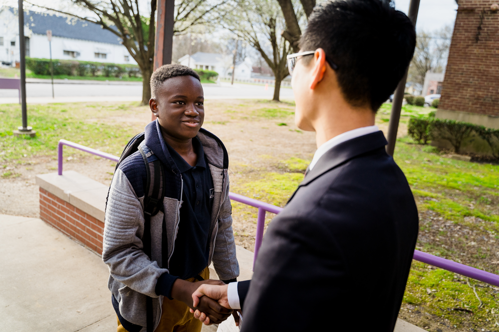 head of school shaking hands with student