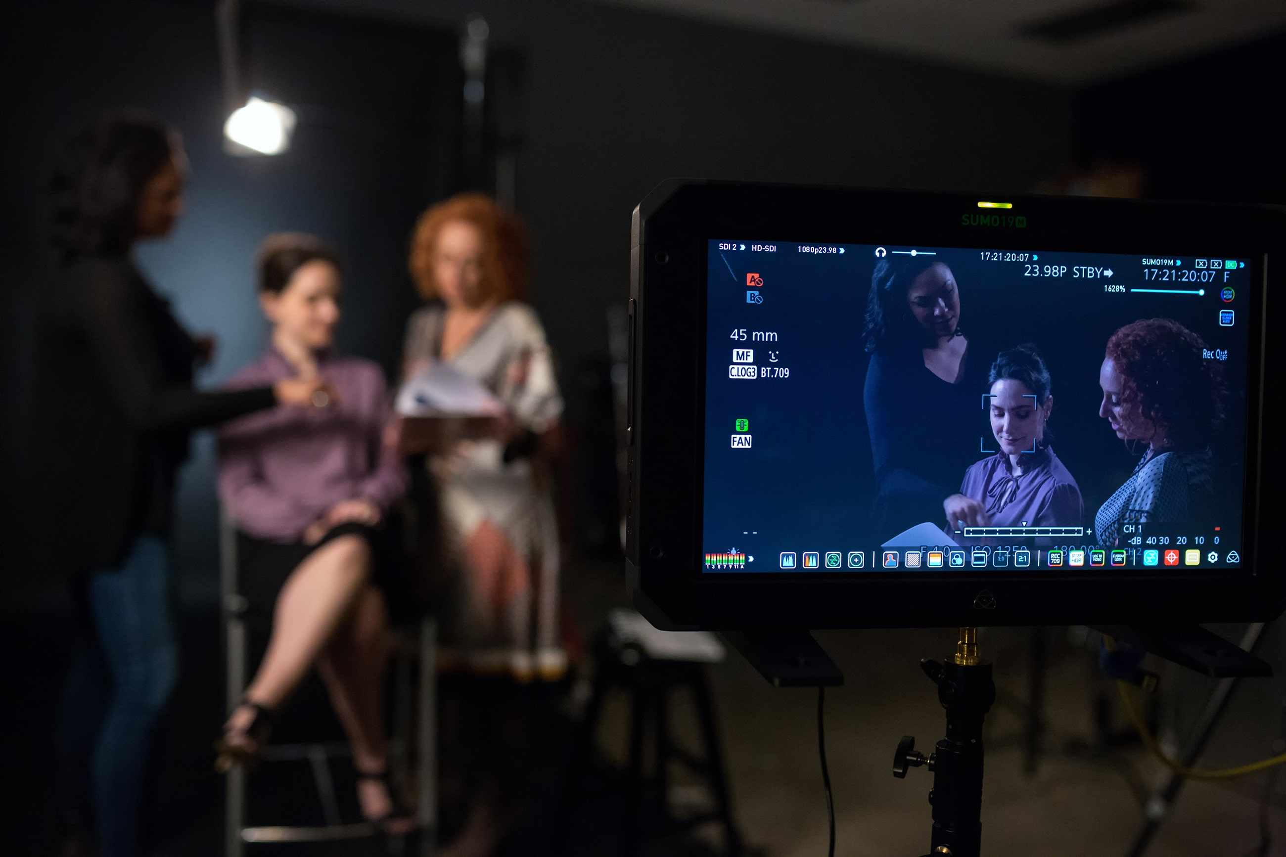 Two women look at footage on a monitor, while a camera is pointed at them in the foreground