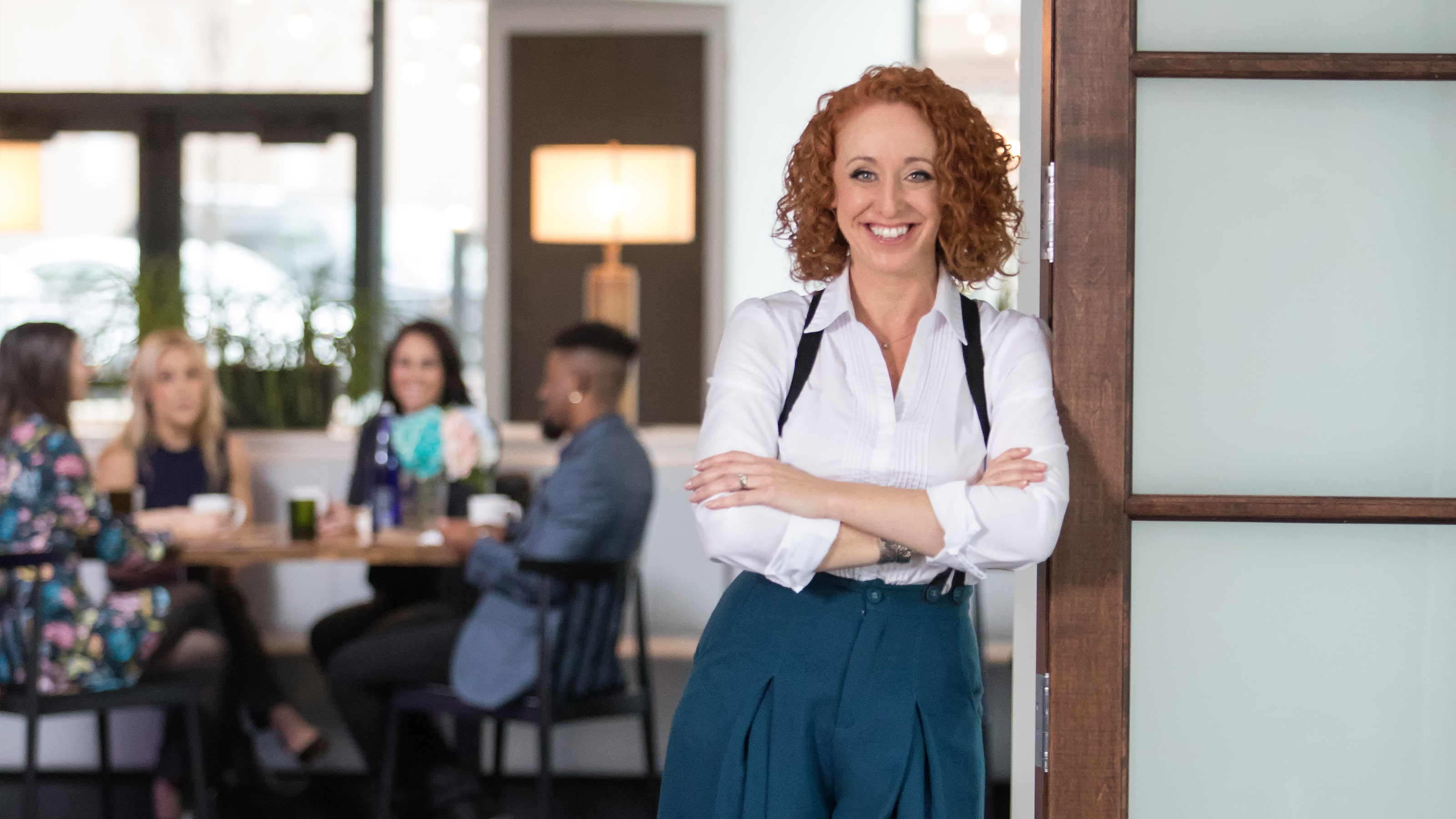 A red haired woman looks confidently at the camera
