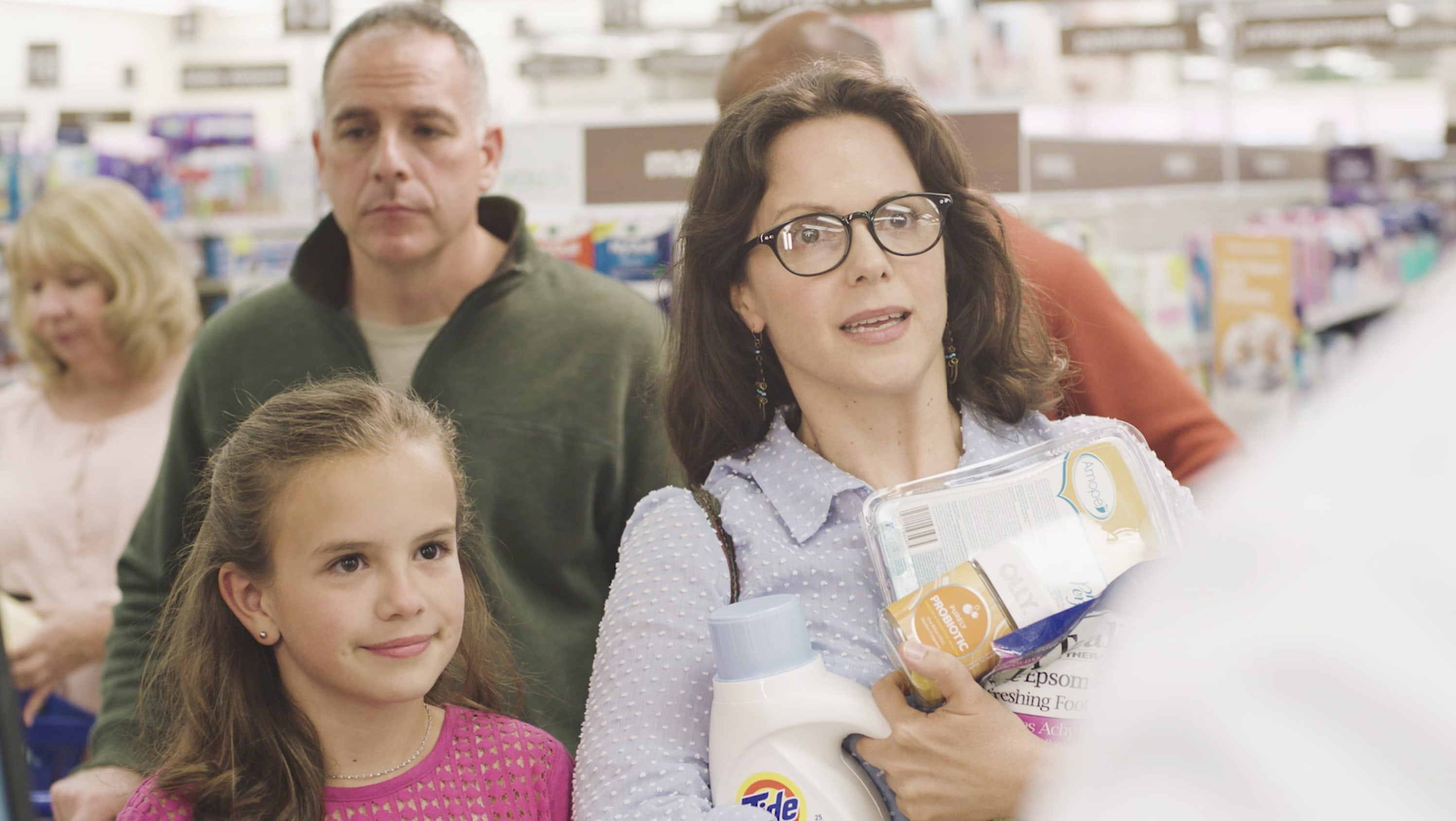 A frazzled, bespeckled mother with many items in her arms stands in line at the store with her blonde daughter
