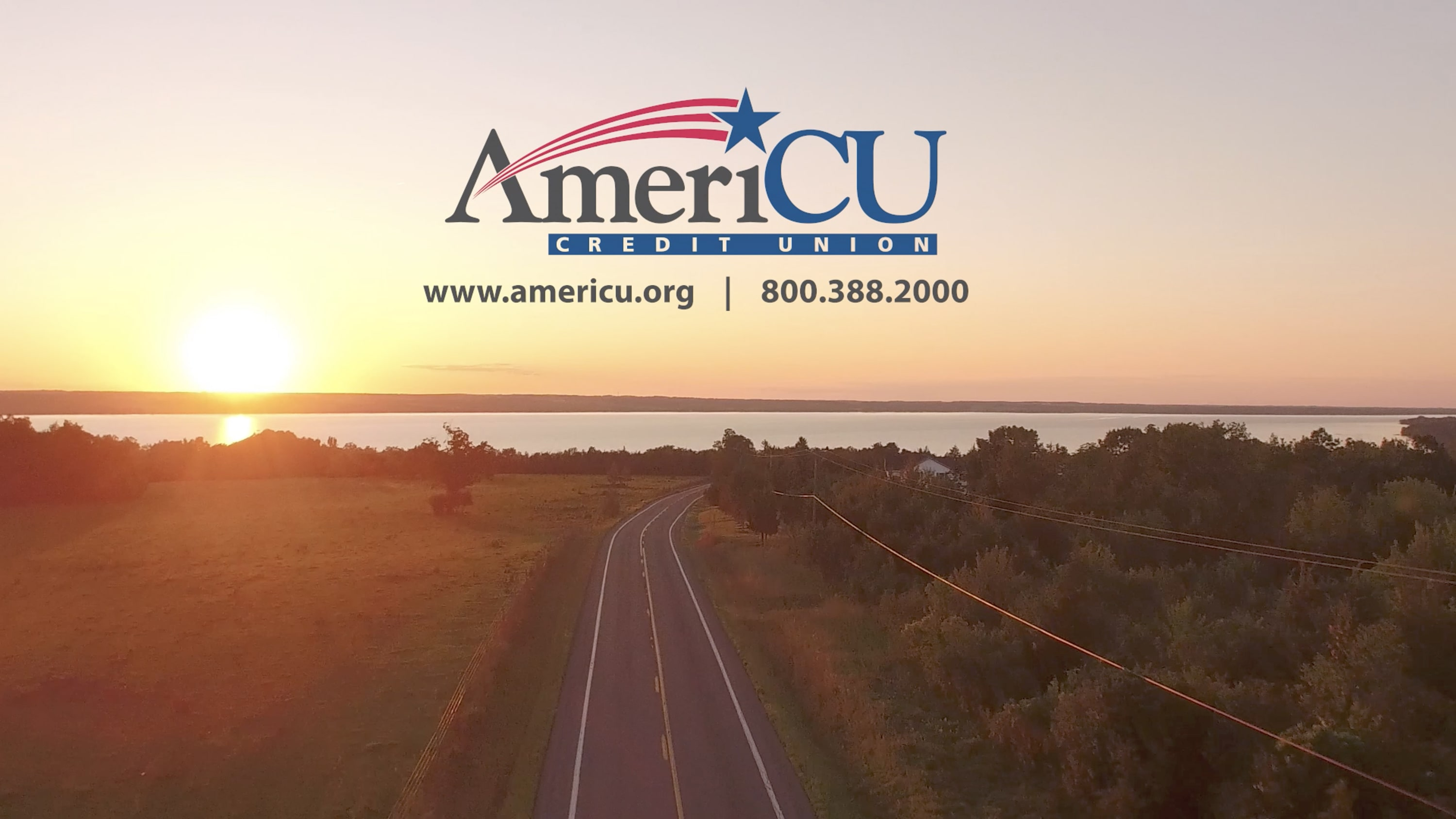 A serene road with the AmeriCU logo over the sunset