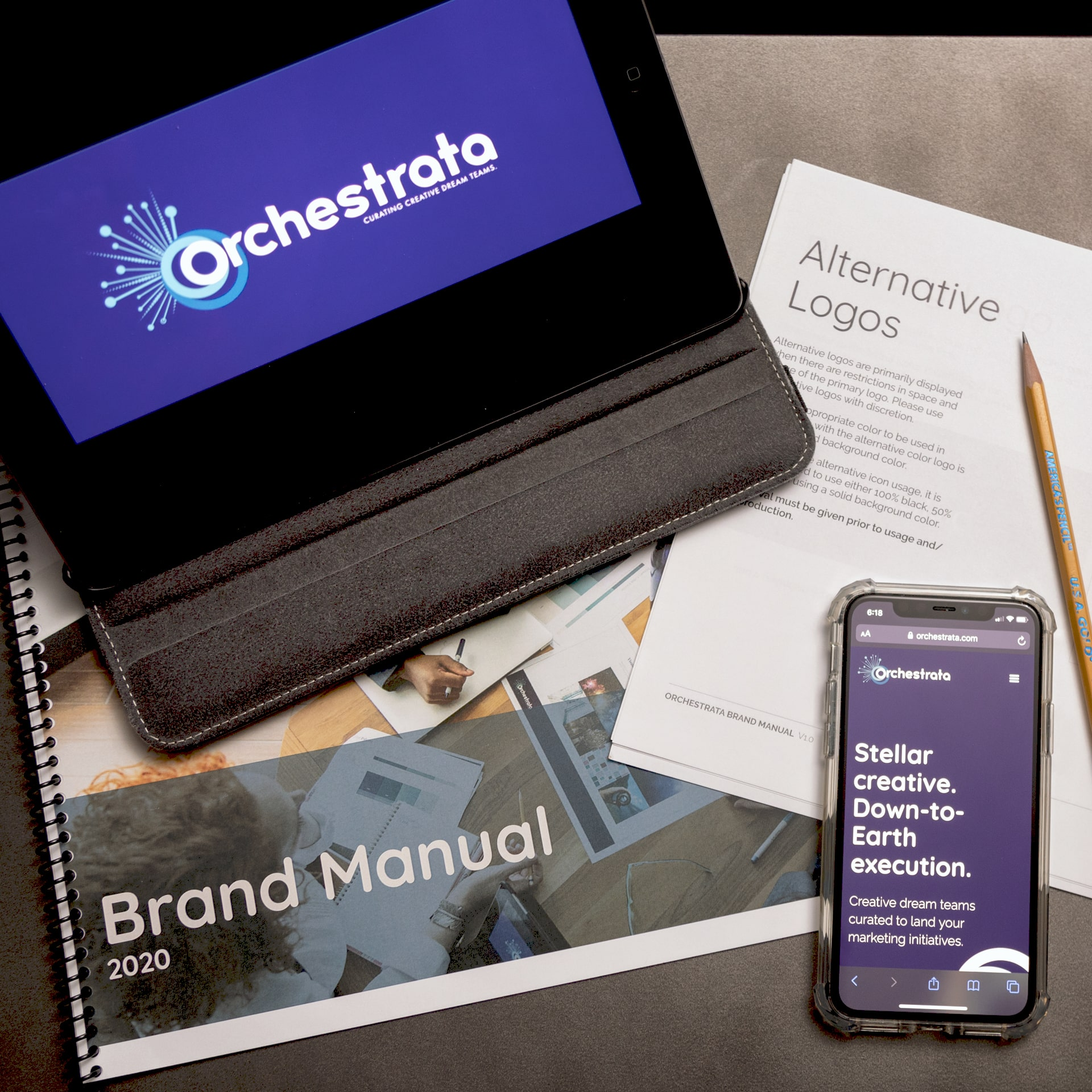 A composed shot of various bluish brand collateral for Orchestrata, including a brand manual, tablet, and website on a mobile phone