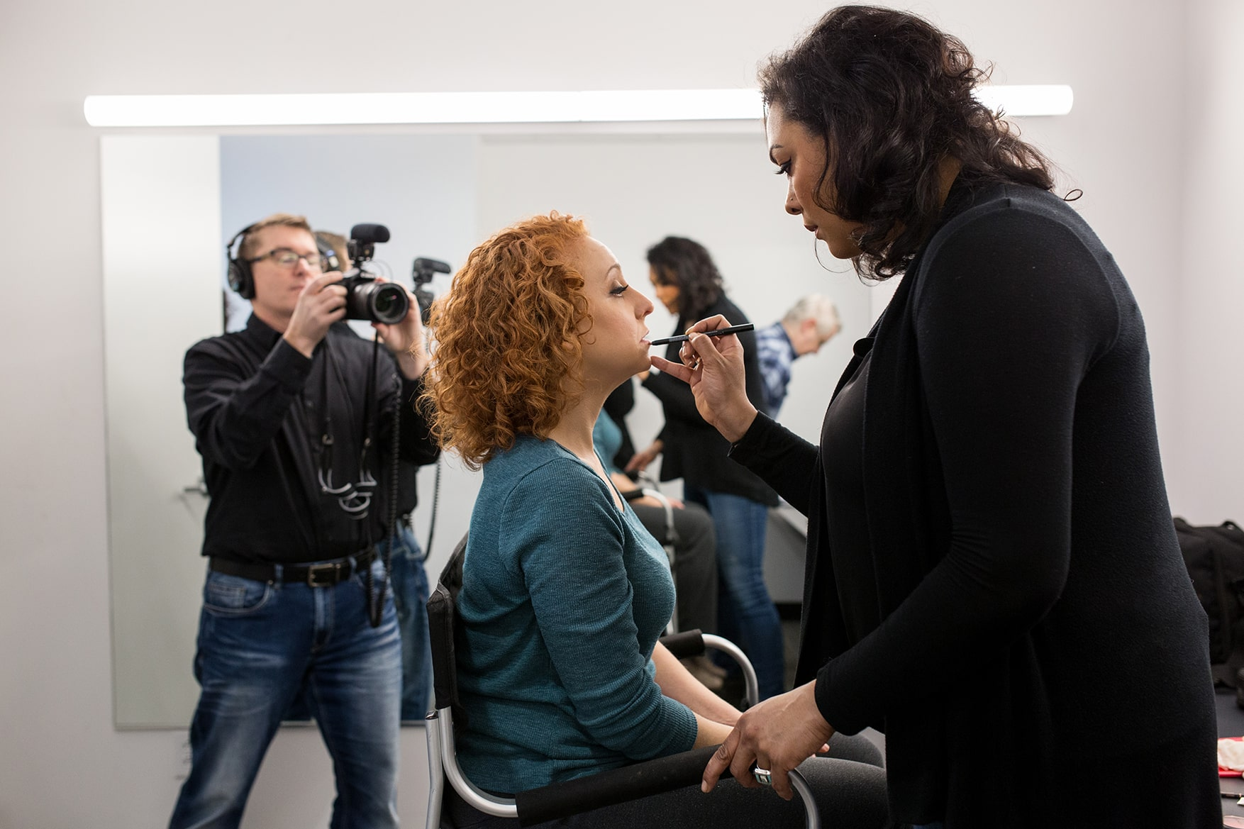 A red haired woman has her makeup applied for a photoshoot