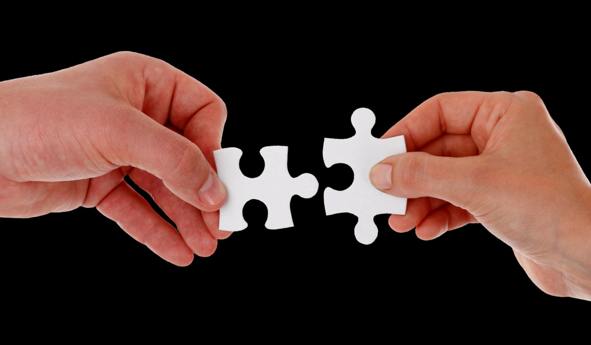 Dues mans amb unes peces de puzle