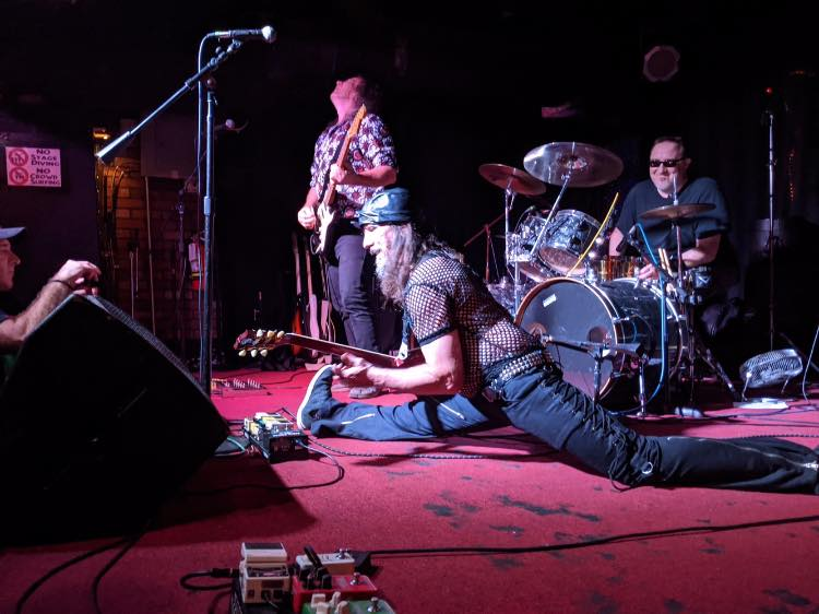 Guitarist doing a split on stage