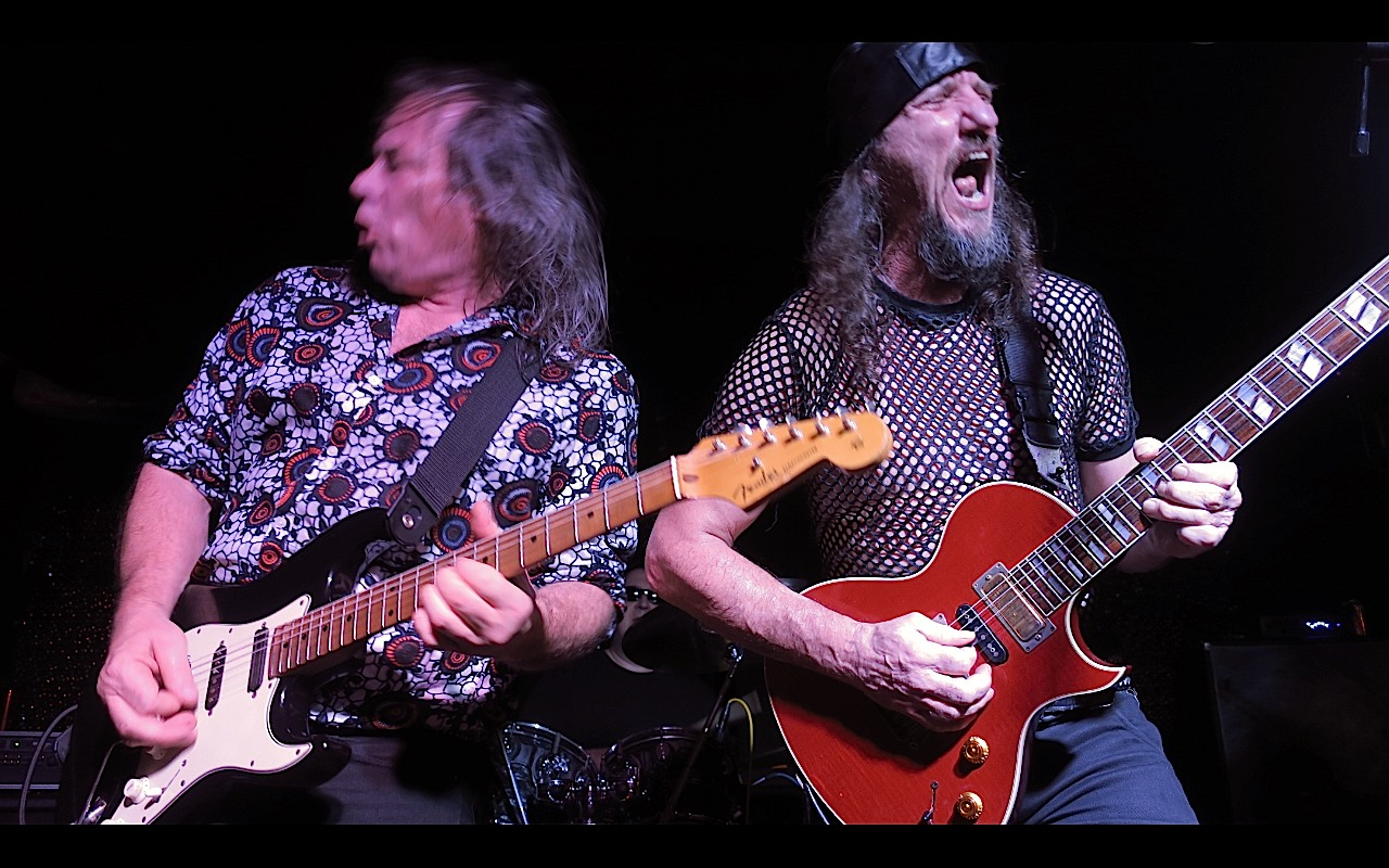 Two guitarists playing on stage together