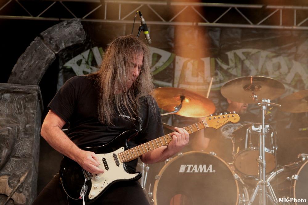 Man with long hair playing guitar