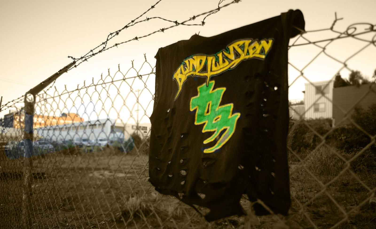 Black tee shirt with green and yellow blind illusion logo hanging on chainlink fence