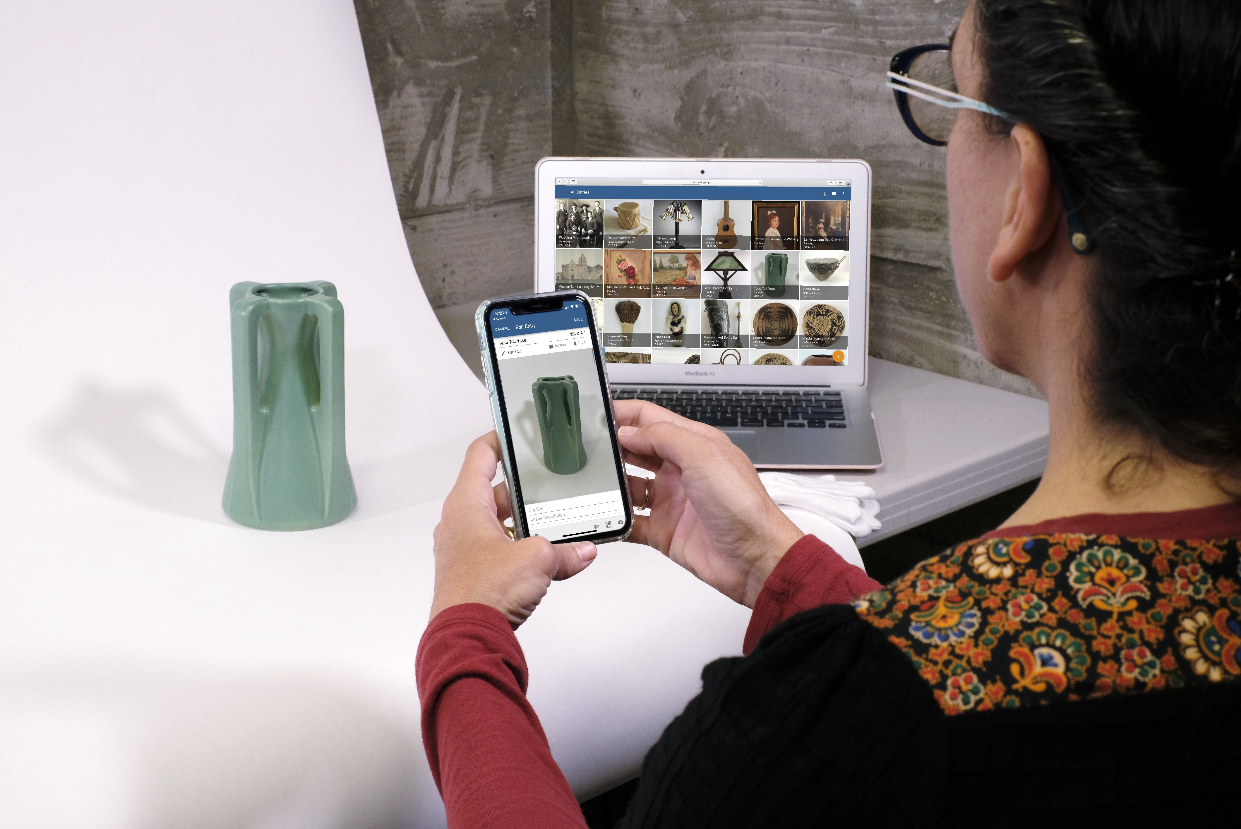 Museum professional cataloging a vase using a mobile device.