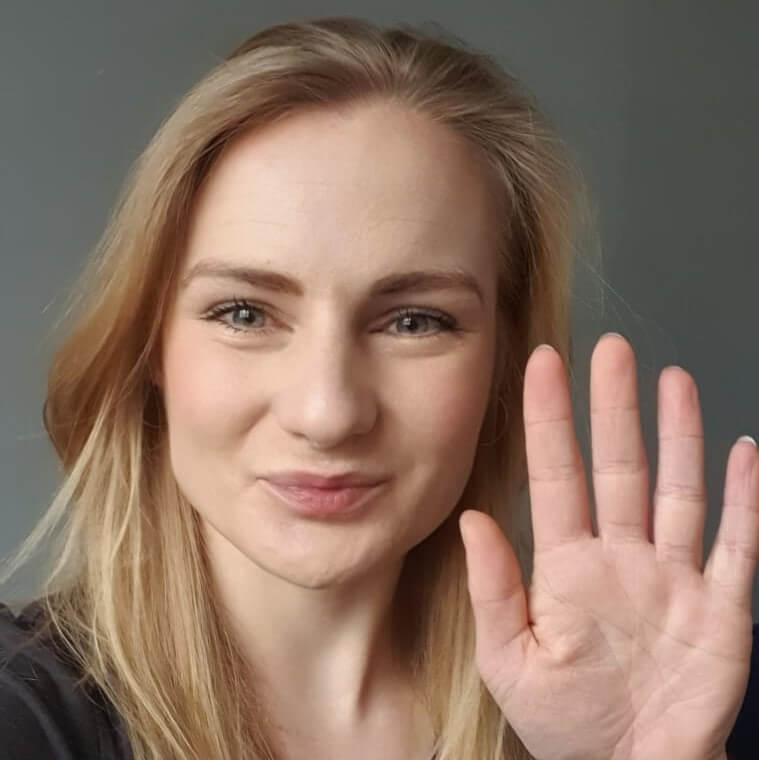 woman holding hand up near face and smiling