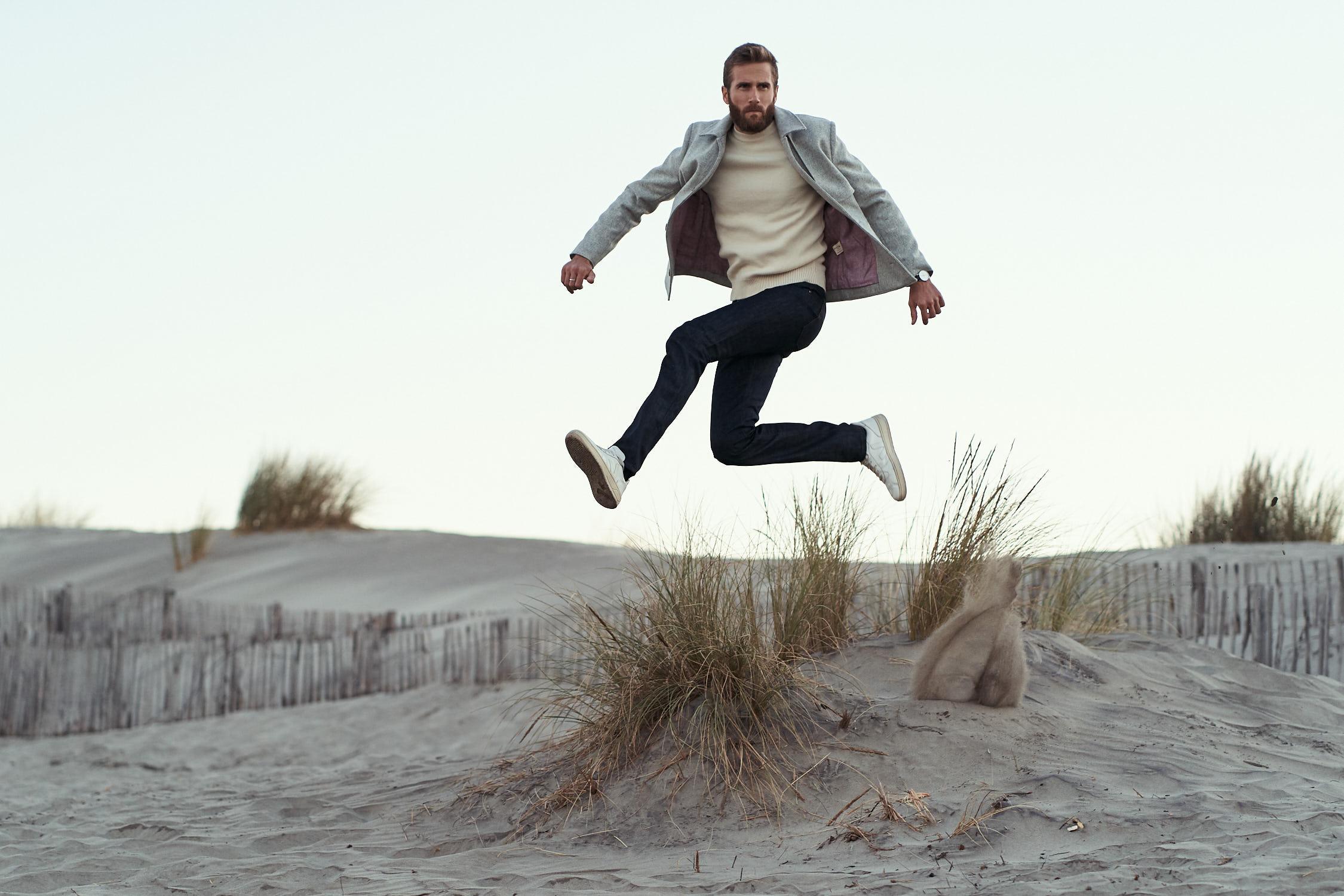 Homme qui saute sur la plage avec un veston en laine gris clair et une doublure rouge en lin belge. Manteau pour homme 100% Made in France