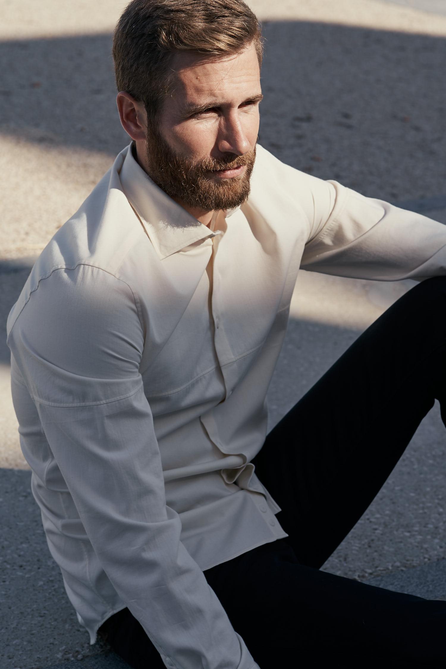 Homme assis portant une chemise  écrue en chambray de coton biologique fabriquée en France par les Ateliers Gauthier. Les boutons sont en corozo
