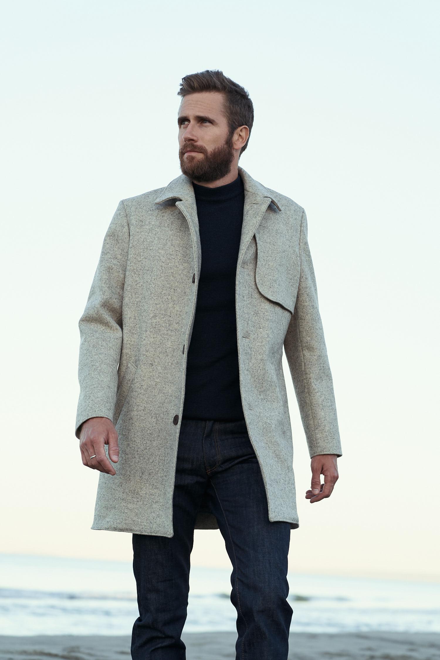 Homme portant un manteau chevrons écru en laines françaises 100% Made in France avec une doublure en lin belge et des boutons en corozo marrons
