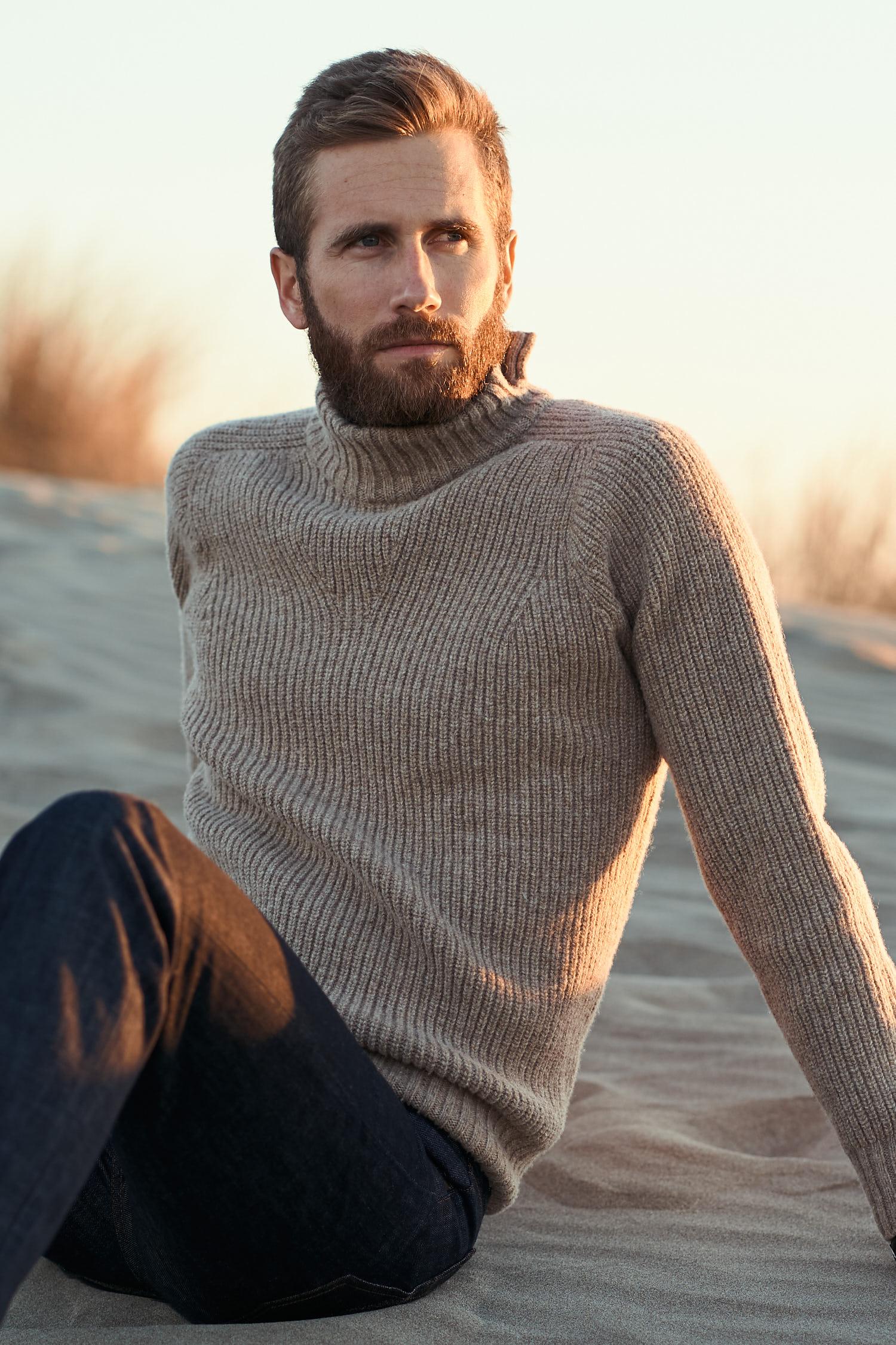 Homme assis portant un pull-over en 100% laine de Mérinos d'Arles, tricoté en France dans le Tarn. La maille est une cote anglaise. Le col est légèrement montant avec une fente sur le côté. 100% Made In France