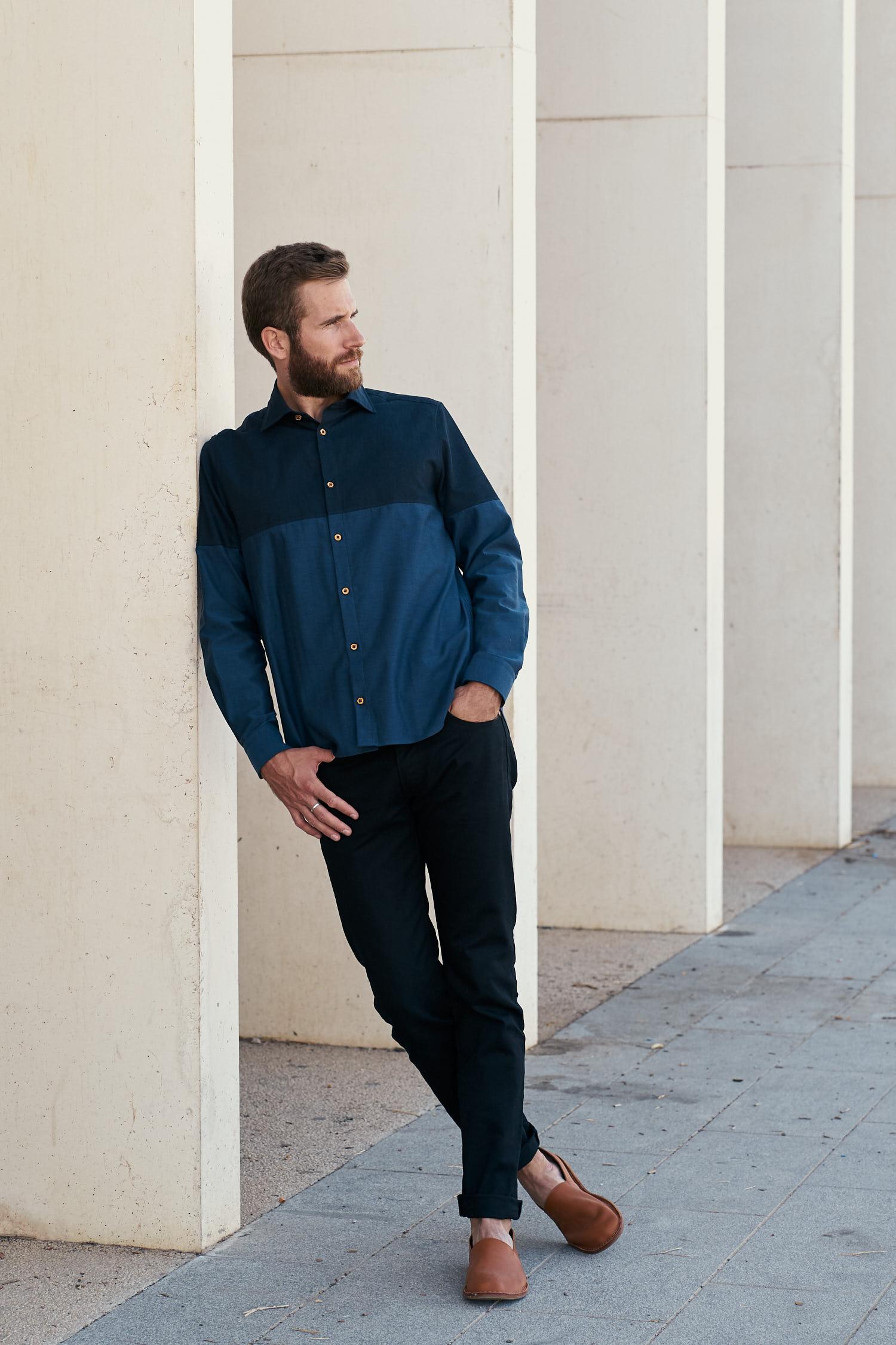 Homme portant une chemise bicolore bleue en chambray de coton biologique fabriquée en France par les ateliers Gauthier. Boutons en bois. Photo prise à la médiathèque de Frontignan. Architecte Tautem