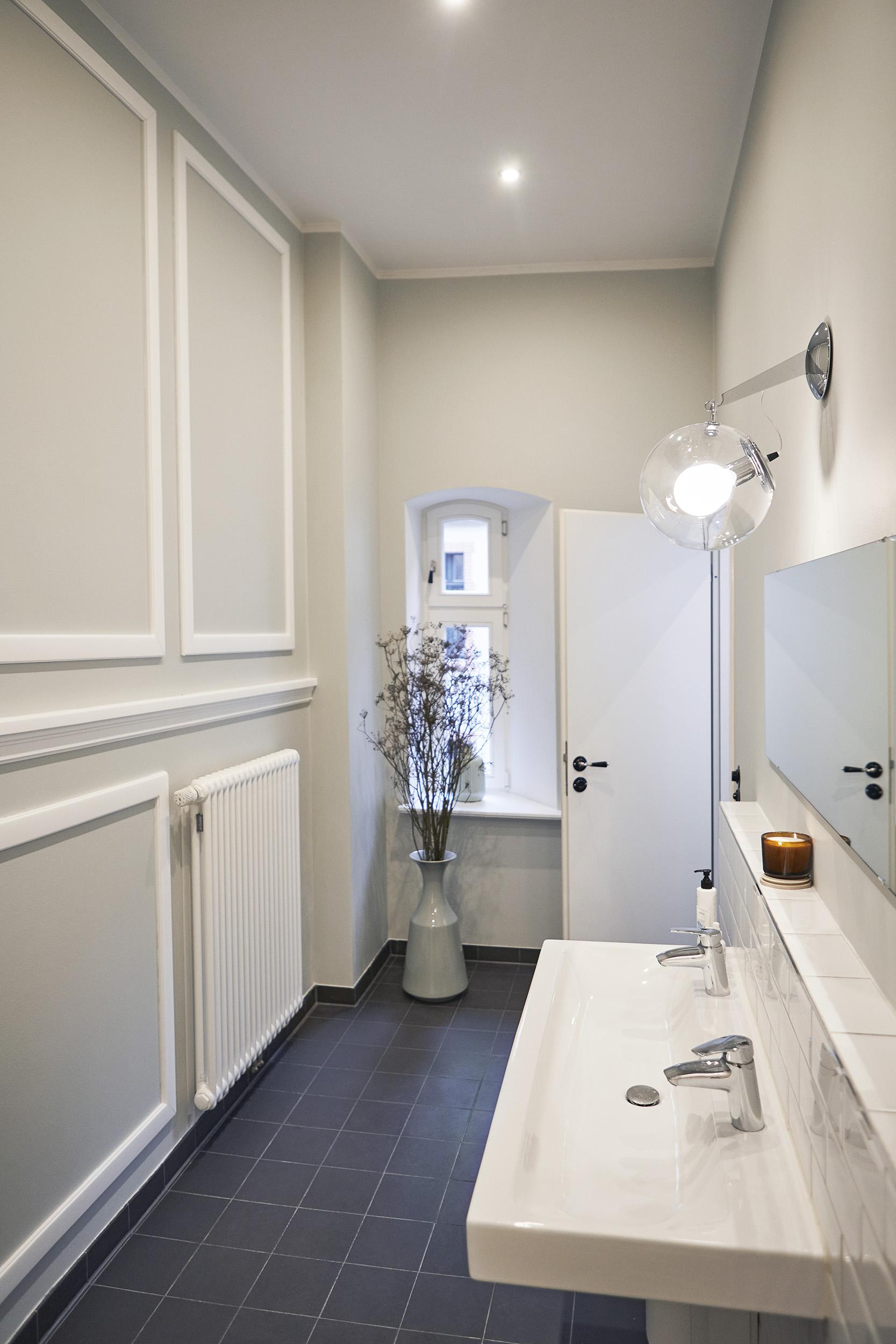 Foto eines Raums mit unverputzten Wänden, gelber Lampe und Tisch