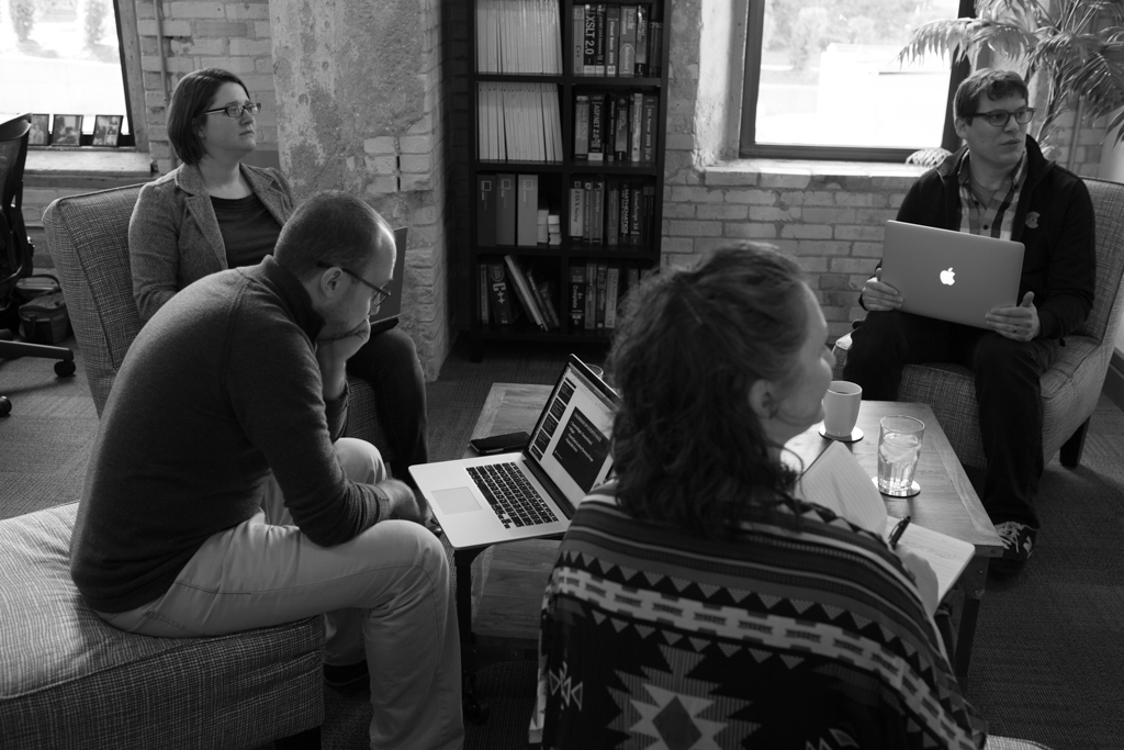 A group of people sit down in an array of couches and chairs while another person writes on a whiteboard.