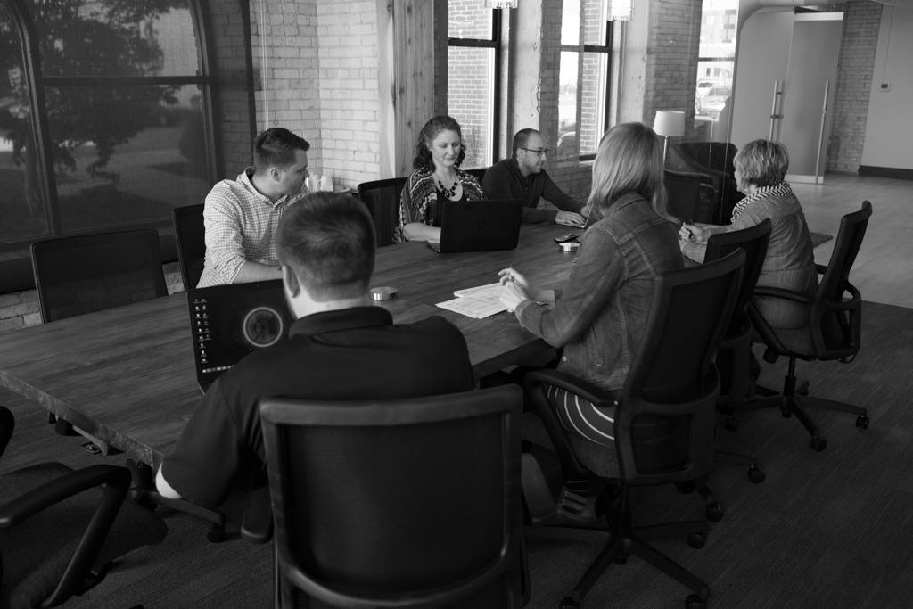 A group of people meet at a large wooden desk and discuss a web project.