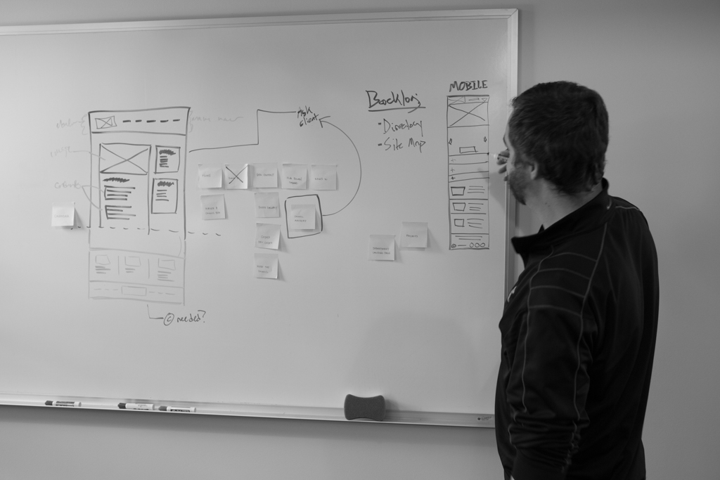 A man sketching out wireframes to a website on a whiteboard.