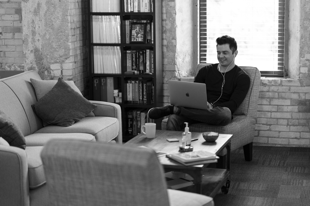 A man sitting on a couch near a coffee table working on his laptop smiling while listening to music.