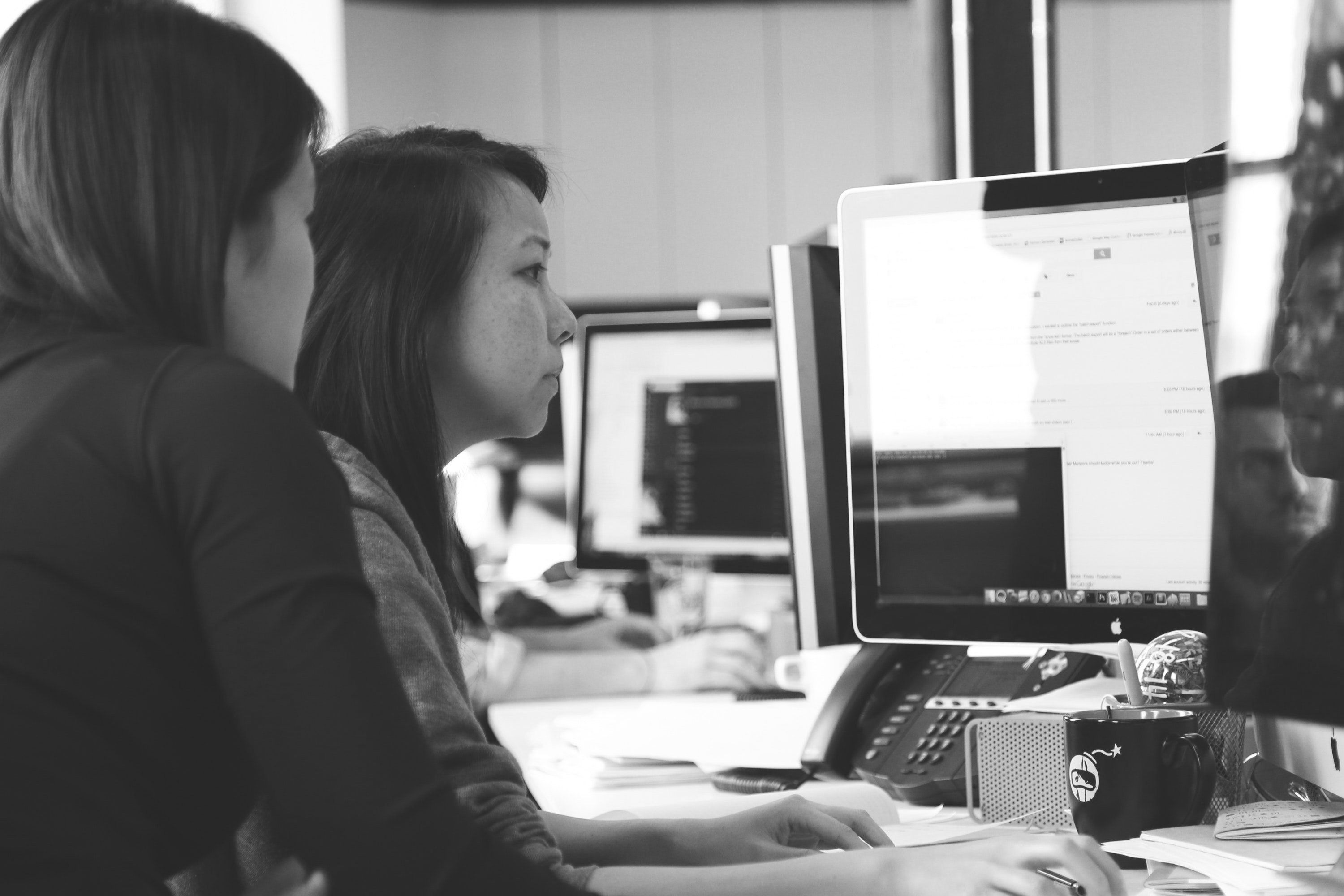 Black and white photo of two women sitting at a computer