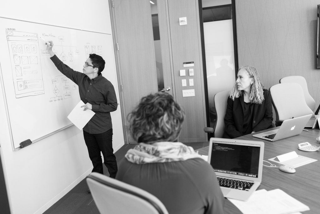 Group of people looking at whiteboard drawings of existing website information architecture.