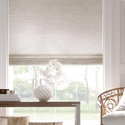 A bespoke shade woven from natural materials in soft neutral colors.